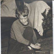 Image of Boy with Royal Blue O Gauge American Flyer Train Set - Young boy in sweater kneels on floor gazing at an O Gauge American Flyer train set on track.  Afghan on sofa in background.