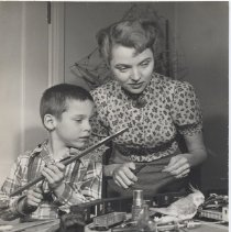 Image of Actress Jane Wyman and Son with Layout - Actress Jane Wyman and son, Michael, play with parrot by toy train layout.  Jane wants to use her drill but pet cockatoo, Jeeves, is using it as a perch.  One of a series of 6 photos.  HO gauge model trains, structures probably scratchbuilt.