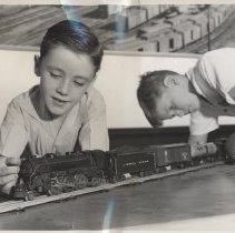 Image of Devotees of Toy Trains - 1945 photo of two boys playing with Lionel toy train.  Promotional photo. Lionel prewar train set pictured is a 224E locomotive, 2758 PRR auto boxcar, and unidentified tank car.  Boys shown are John O'Connor and Clyde McDowell.