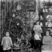 Image of Christmas Scene, Girl with Doll Carriage and Boy with Toy Train Layout - Mother with arms crossed, girl with doll in carriage, boy with toy train on Christmas raised floor layout. Clockwork Steam engine and tender with 3 passenger cars.