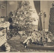 Image of Christmas with Toy Trains, Soldiers and Creche - Photo of elaborate Christmas scene.  Pewar Lionel toy train layout on raised platform on floor with buildings, scenery and tunnel.  Large creche.  Army of toy soldiers.  Cradle and doll. Chimney and Santa Claus.