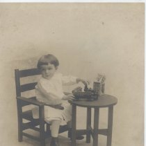 Image of Young Boy with Cast Iron Train Set - Photo of young boy in white dress sitting at child's table with cast iron floor train set..  Train is Ideal of 1899 (ref, Ralston item #284, Page 79.)