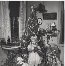 Image of An Old Fashioned Christmas - Posed photograph.  From Ward Kimball collection.  Appeared in TTOS Bulletin.  Photo by Ward Kimball. Small girl surrounded by antique toys from Ward Kimball's collection.  Includes wood and paper litho train set, boats, cast iron train set, large bicycle, dolls, books and more. Photo appeared in TTOS Bulletin and ? Train Collectors Quarterly.