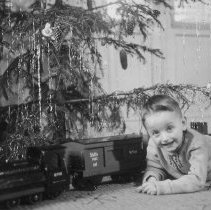 Image of Happy Boy - Boy with large scale wooden train set of European prototype.