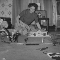 Image of Fun with Trains - Young boy and Mother with a clockwork train set and accessories.