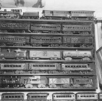 """Image of Ben Smith Toy Train Collection - Seven shelves of a variety of toy trains ranging from Roberts Lines """"Pioneer"""", Bing and American Flyer Standard Gauge             (1925-27) American Flyer O gauge freight cars (gondola, box and tank cars)  Ives Saratoga set, Flyer freight & Ives White Owl cars at bottom right."""