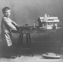 """Image of LaRue Shempp at Age Four. - TCA charter member and collector Extraordinaire, LaRue Shempp, at age 4 in 1915 at train platform with Ives #17 clockwork locomotive and O gauge passenger car with a Schieble HillClimber boat* and Hubley cast iron fire truck on the floor. The train station is probably Schoenhut of Philadelphia, made for both Ives & Lionel.  Shempp's collection is the focus of """"Toy Train Treasury"""" Volume II.  *See page 28 of R. Claus """"Alure of Toy Ships""""."""