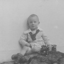 Image of Young Boy With a Pull Toy Train - Young boy with a pull toy train of European design.