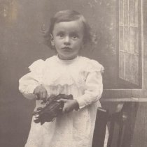 Image of Boy with Toy Locomotive - A professional photograph of a boy holding a steam type floor locomotive about 'O' gauge size.  Looks to be Bing clockwork with the little boy holding the wind-up key in his right hand.