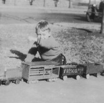 """Image of Proud Young Man with his Train. - Wooden train consisting of steam locomotive, tender and five freight cars. probably home made by a very clever parent or Junior and parent. During the Great Depression factory made toys were seldom purchased and many parents resorted to making their own. Onder magnification the """"FRISCO"""" lettering appears to be home made rather than professional."""