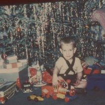 """Image of A young boy with a Fisher Price 1963 """"Huffy Puffy"""" toy locomotive & tender pull toy.  Other metal toys include a bus, police car and open wheeled race car."""