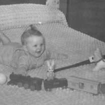 Image of Baby & Train - Baby lying on bed with a wooden train and other toys.