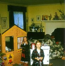 Image of Boy and Girl at Christmas - Two children in a Christmas scene with a train station on the left, either plastic or metal.