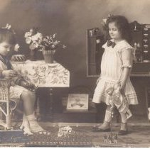 Image of Boy Sitting in Wicker Chair, Girl Standing, with Toy Train - Italian postcard. Boy and girl in photo. Boy sits on wicker chair. Girls stands, holding doll. Toy train runs around track at their feet. Train is by Bing (2B) with 6 wheel tender made in 1910-1914 and equipped with an 18 volt motor.