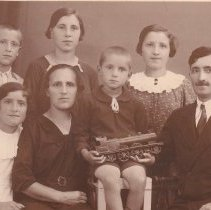 Image of Hungarian Family with Boy holding Locomotive Toy Train - Photo/postcard of Hungarian family of seven.  Youngest boy in photo holds toy locomotive.  British style locomotive.  Stamped steel construction per Bassett-Lowke design.