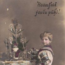 "Image of Boy in Sailor Suit Standing in Front of Table with Toys - Postcard from Estonia. Small boy in sailor suit stands in front of table with Christmas tree on it. Under the tree is a Santa Claus, horn and toy locomotive. Toy locomotive is by Schoenner, Live steam with ""Wind Cutter"" boiler front, O gauge."