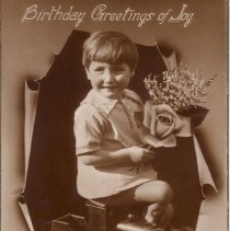 Image of Birthday Greetings of Joy - Boy sitting on a wooden riding toy locomotive.