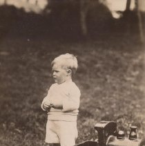 Image of Sunshine Baby - Wooden riding train with young boy standing beside it.