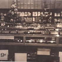 Image of Hardware Store Toy Train Display - Interior of hardware store showing toy train display cases.  Trains are Lionel O gauge, top shelf contains #263E loco, #615 baggage car, #613 pullman car, # 614 observation car, #646 power station, #83 traffic signal & #45N automatic gateman, all c. 1937. Second row from top contains #259E loco, #607 pullman, 2- #608 observation cars, Rail Chief #700E loco, #792 combination, #793 coach & #794 observation.  Third row from top contains #249E loco, #600 pullman, #601 observation, #226 loco, #2615 baggage, #2613 pullman & #2614 observation car.  Bottom row contains #700E loco, #2600 pullman, #2602 baggage, #2601 observation.  Photo details identified by Jim Yocum.