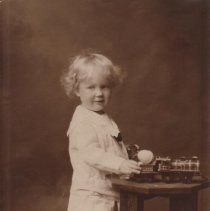 """Image of Ned Alter, Baby, with Toy Locomotive on Table - Toddler photo of child, Ned Alter.  He stands beside table with  his hand on toy locomotive w. tender.  Train is a lithographed floor toy 10-1/4"""" long #714 locomotive with NYC & HR tender, made by J. Chein & Co. c. 1915-1920.  Train was used as a prop by a professional photographer.  Train identified by Phil Ritter."""