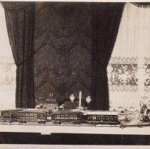 Image of Toy Train Passenger Set on Table by Windows - 1927 photo postcard of a toy train passenger set and station on table in front of windows.  The items shown in the photo are:  #10252 oil burning arc lamp c. 1912, #7042 Bing railway station c. 1910-1928, #1887/1 Marklin post wagon c. 1919, #1894/1 salon, #1894 dining car, # E3141 locomotive & E1860/1 tender, #10403 Bing signal c. 1912 & #10115 Bing goods station.