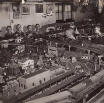 "Image of Boy Scouts with Large Toy Train Layout I - Boy Scouts operate trains at very large toy train layout.  Track is Gargraves, buildings are Plasticville and Skyline.  Trains are mostly Lionel such as #47 crossing gates, #2023 Union Pacific Locomotive - type I, #2343 A-B-A unit pulling 3 - #2530 railway express cars, #2531 Silver Dawn & #2532 Silver Range (other cars in train unidentified, #145 auto gateman, #157 illuminated station platform, #445 operating switch tower, #2481 pullman, #2482 pullman, #2483 observation & ZW transformers.  There is also a Kusan ""Pennsylvania"" F-7 A-A unit pulling Lionel madison cars.  Photograph details identified by Jim Yocum."