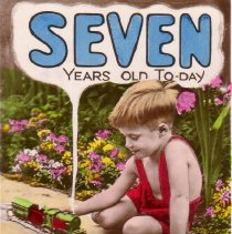 Image of SEVEN YEARS OLD TODAY - Young boy playing with train out of doors on a birthday post card.  Train is Hornby O gauge clockwork.