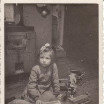 Image of Mother, Father and Small Girl on Floor with Wooden Train Set - Photo from Russia.  Mother, father and young girl on floor with large wooden toy train set.  There are two similar pictures, 002 is of just the young girl with same background and train.