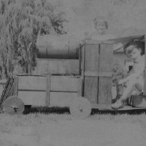 Image of Boy and Girl on  Large Wooden  Locomotive - Photo negative from 1933.  Boy and Girl play on large wooden outdoor  locomotive.  The locomotive is believed to be home built.