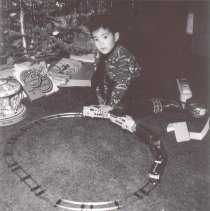 Image of Christmas Day! - Boy playing with new train set next to Christmas tree on Christmas Day.  Train is a Marx #735-D clockwork version of the Union Pacific M10005.  (Train identified by Jim Yocum.)  Other toys in picture are a Merry-go Round and a car carrier.