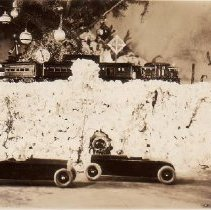 "Image of Christmas Morn! - Christmas platform layout with American Flyer O gauge trains c. 1925/1926.  Include #1207 observation car, #1205 baggage car ""Chicago"", #1206 passenger car ""Seattle"", #1218 electric outline steeple cab locomotive, #206 Danger Signal & Departure Clock."