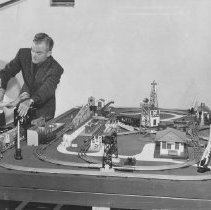 Image of Spike Jones Commercial for Lionel Trains - Spike Jones making a TV commercial for Lionel. Layout built in the shop of Art Truman. Visible in the picture are a ZW transformer, Santa Fe F3, coal dump car, operating cattle car, operating log car, operating hopper car, 151 semaphore, 364 log loader, 456 coal ramp, 145 gateman, 362 barrel loader, 3656 cattle platform, 3462 P milk platform, 452 signal bridge, 394 rotary beacon, 442 switch tower, 455 oil derrick, 356 freight station, 153 block signal, 252 crossing gates and 132 station. All items from 1-7-08-01 to 1-7-27-02 are photographs or data on Art Truman layouts.