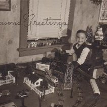 Image of Christmas Card with Boy Playing with American Flyer Layout - Seasons Greetings, A photographic print used as a Christmas card.  Young boy playing with American Flyer S gauge layout.  Shown are a #769A revolving aircraft beacon w/o shed, Union Pacific Northern steam locomotive, #718 New Haven operating mail pickup car, #625 Shell tank car, #905 log car, #635 crane car, #632 LNE hopper car, #21115 K-5 Pacific steam locomotive w/tender.