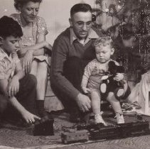 Image of Father, Mother and Two Children with Toy Train around Tree - Father, Mother, and two children sit near Christmas Tree.  Son operates transformer for Lionel locomotive and caboose.  Trains are Lionel O gauge, #2025 locomotive (PRR K-5 Pacific), #24WX tender and #6257 SP caboose.