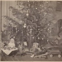 Image of Photos of Toys and Station under Christmas Tree - Photo of many toys and station under Christmas tree.  Die Cast floor train, Bing water tower, dolls, wagon, trolley, station, tea set, rocking horse, toy animals, books and more.
