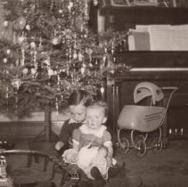 """Image of Boy Holding Baby Sits on Floor with Toy Train - Boy sits under Christmas tree holding baby.  He sits next to elevated toy train set.  Doll carriage in background.  Train Set is Marx """"Commodore Vanderbuilt Trestle Set""""  Research by Jim Yocum."""