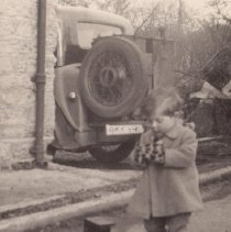 Image of Boy with his Train - Boy standing next to a pull type wooden toy locomotive lettered for the LMS (London Midland and Scottish Railway) in Great Britain.