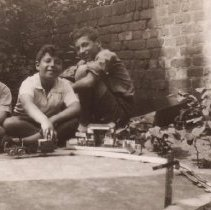 Image of Three Boys Outdoors with Train Set - Postcard from England.  Three young boys sit and kneel in front of wall, playing with toy train set.  No information on trains.