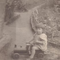 Image of Child in Garden on Ride On Toy Locomotive - Small child sits in garden on toy locomotive, this is believed to be in England.  The wooden locomotive looks to be a manufactured item but can not be idenified as to manufacturer.