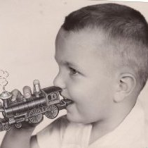 Image of Young Boy with Toy Train Whistle - Young boy holds toy train whistle by Eljay in mouth.  May be an advertising photograph.