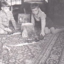 Image of Two Boys with Circle of Track and Toy Train on Floor - Two small boys play on oriental carpet with Bing clockwork passenger set on a circle of track.