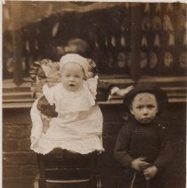 """Image of Baby in High Chair and Young Boy with Large Pull Train - Photo postcard of baby in white dress in high chair and young boy standing, holding string to large pull train.  On back, card reads,"""" V.A. Parkinson, died 28 Sept. 1909."""