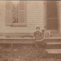 Image of Child on Porch with Dog and Toy Train - Child, R. Gregory Fisher, 4 years old, and Punch, his dog, sit on porch with toys including what looks to be a floor train.