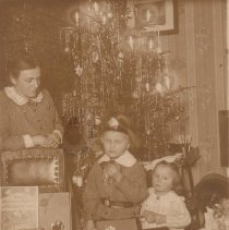 """Image of Mother, Girl and Boy in Front of Christmas Tree with Toy Train - Mother, boy and girl stand in front of Christmas tree and display Christmas toys, including toy train.  Train is an unidentified """"carpet train""""."""