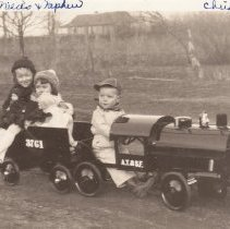 Image of 3 Children on AT&SF Ride-On Toy Train - 3 Children on large home built (built by Uncle Harold) ride-on AT&SF locomotive #3761.  Turkeys in background.