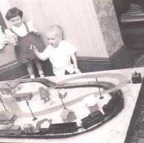 Image of Young Girl and Boy Stand Beside Toy Train Layout - Young girl and boy stand beside toy train layout in home.  Marx train set with NYC caboose, crane car, Lehigh Valley hopper car, NYC tender and unknown steam locomotive.  Cardboard cutout buildings.