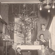 Image of German Family Photo with Christmas Tree & Toy Trains - German family photo with family and child sitting and standing around Christmas tree with toy train set on floor.  Train set looks to be Bing, but not enough detail to be sure.  Track with light colored ties is a puzzle.