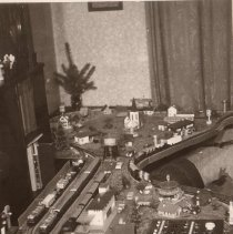 Image of Toy Train Layout with Small Christmas Tree - European HO or OO gauge train layout with small Christmas tree in background.  Track appears to be 2-rail.  Print is to small to view details.