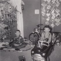 Image of Two Boys with Toy Train Set and Ride-On Car - 1954 photo of 2 boys on Christmas day. One sits in ride-on car and the other sits on floor with toy train set. Train set appears to be a Lionel 2234W O gauge set with a 2350 baggage car which first appeared with this set in the 1954 catalog. This set is shown on pages 28 & 29 of the 1954 catalog. Conflicting with this is the 1947 date penciled on the back of the print, probably added years later from memory. This set sold for $89.50 less transformer in 1954, a relatively expensive set for the day.