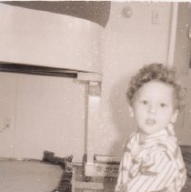 Image of I'm an Engineer - Young boy plays with train set under piano.  Train is a Lionel work train set.